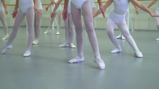closeup legs of little ballerinas group in white shoes practicing in classical ballet studio