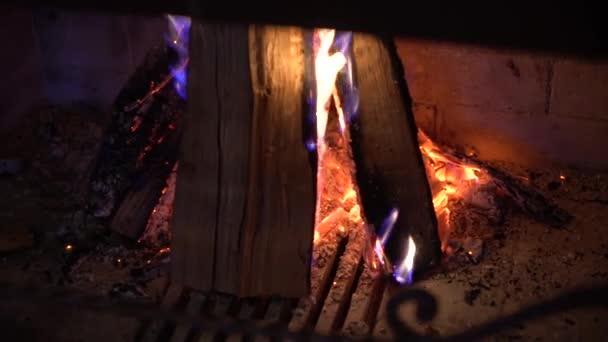 Detailní záběr na hořící dřevo v krbu ve tmě