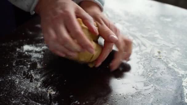 Closeup žena rukou hnětení Syrové těsto na stůl pokrytý mouky