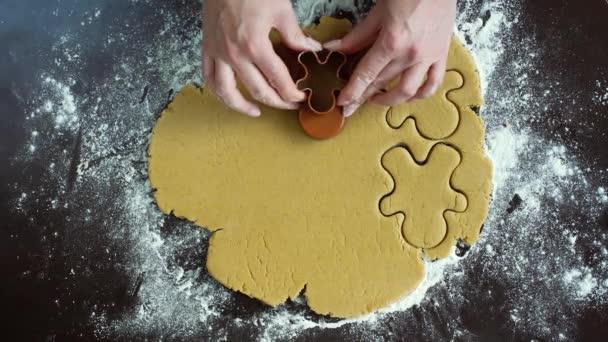 žena ruce řezu panáčka soubory cookie ze syrového těsta pomocí frézy pohled shora
