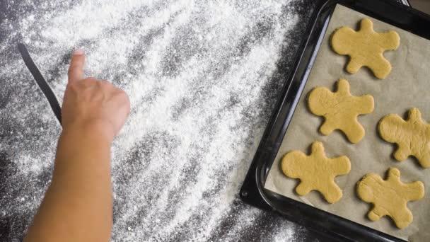 pohled shora ruky člověka psaní Vánoce na mouku zahrnuty tabulka s cookies muže perník na plech