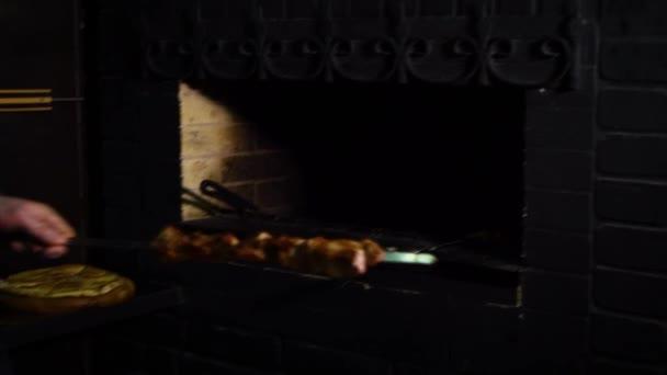 muž při špejle s pečené maso z trouby a přijímání kusů masa mimo špejle