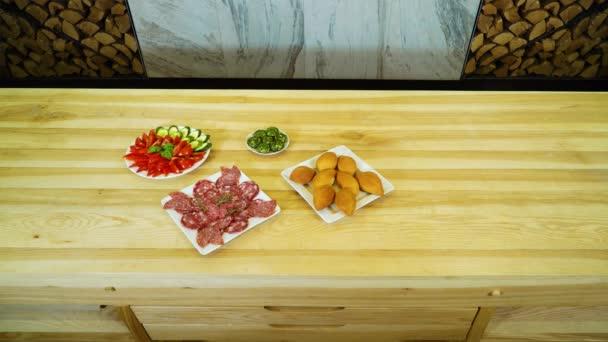sortiment chutných jídel na velký dřevěný stůl