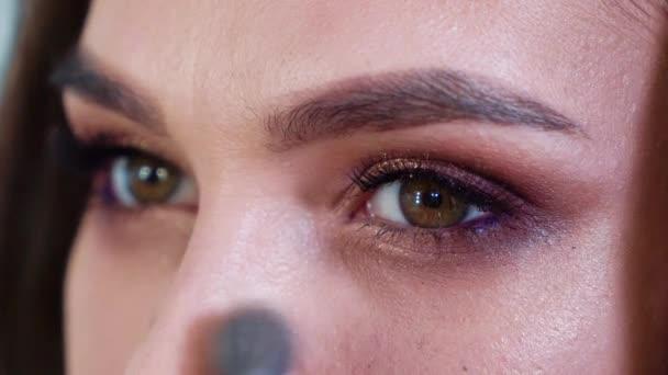 Detailní záběr mladá žena použití pudr v pomalém pohybu. brunetka použití kosmetiky čelit s kartáčem. Krása, make-up a kosmetika