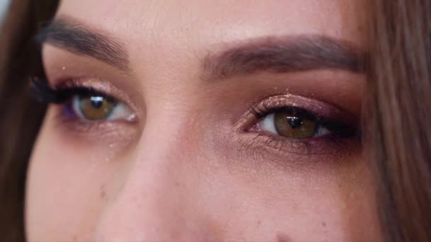 Closeup view of young woman eyes with makeup in slow motion