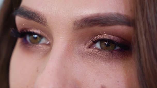 Detailní pohled na mladou ženu oči s make-upem v pomalém pohybu
