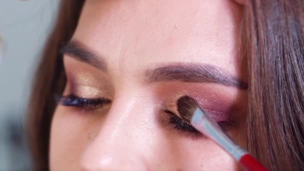 Closeup of hands applying shiny eyeshadows to young woman eyelids in slow motion