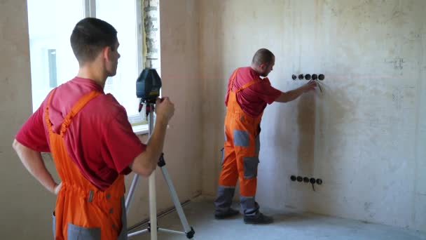Építőipari munkások, hogy mérések lézeres eszköz, az építési telek. Férfi munkavállalók ellenőrzés a piros fény szint pontosság a betonfalnak. Biztonsági politika, a technológia, a javítás, a lakberendezési koncepcióját