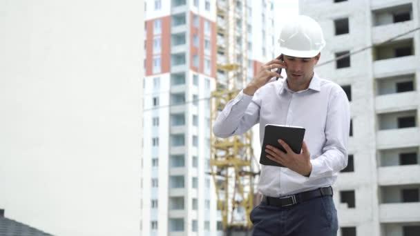 Stavební Web inženýr s tabletem, mluví o mobilní telefon kontrola technologie procesu vytváření. Mužské architekt v průběhu prací prvky bezpečnostní přilba venku. Průmysl, stavebnictví, bezpečnostní koncepce