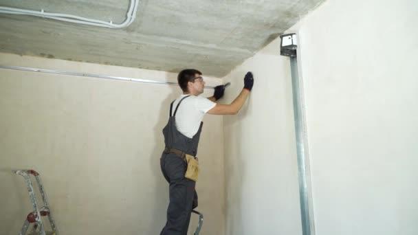 Arbeiter mit Schutzhandschuhen und Brille markieren auf der Baustelle mit Bleistift die Wände. Industrie, Bauwesen, Sicherheitskonzept