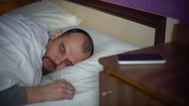 mladý vousatý muž spí v posteli
