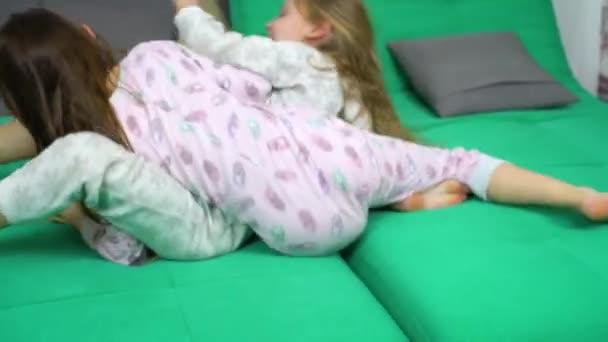 két gyerek harc a kanapén párnák