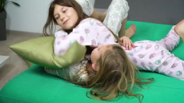 two kids in pajamas fighting on sofa
