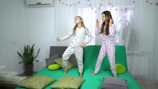 zwei nette Mädchen im Schlafanzug auf Sofa tanzen