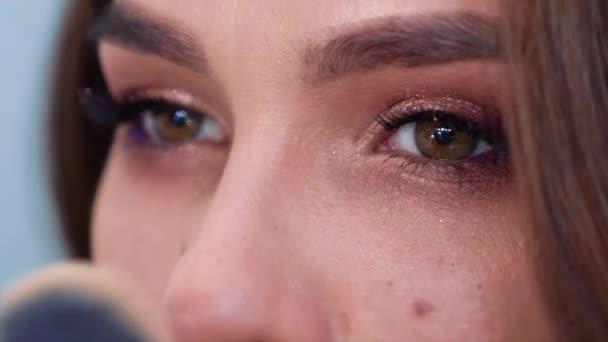 Closeup mladá bruneta žena použití pudr v pomalém pohybu