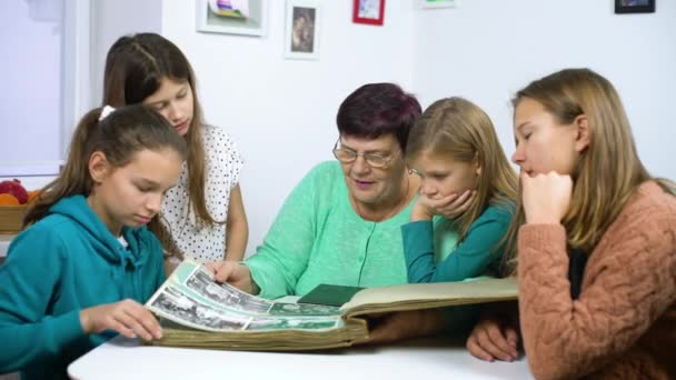 Babička zobrazeno staré fotoalbum k její vnučky. Starší žena ukazuje černé a bílé fotografie dětí. Rodina, vztahy a komunikace