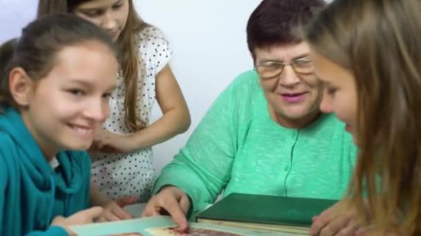 Closeup babička zobrazeno staré fotoalbum k její vnučky