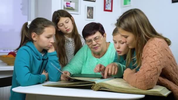 Grandmother showing old photo album to her granddaughters. Senior woman showing black and white photos to children. Family, relationship and communication