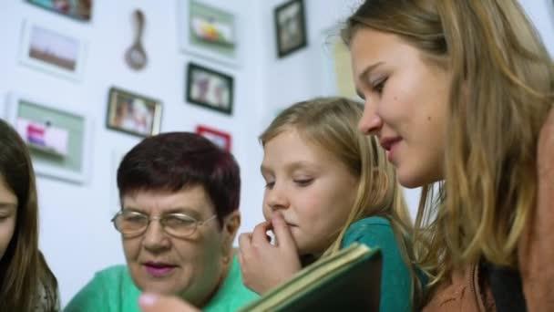 Closeup babička a čtyři vnučky sledovat staré fotoalbum doma