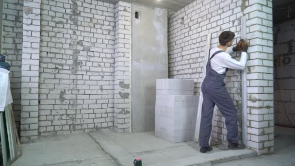 construction worker doing markup on wall according to laser level