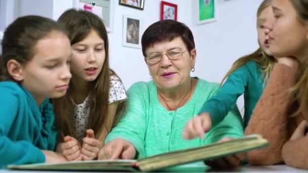 Babička zobrazeno staré fotoalbum k její čtyři vnučky. Starší žena ukazuje černé a bílé fotografie dětí. Rodina, vztahy a komunikace
