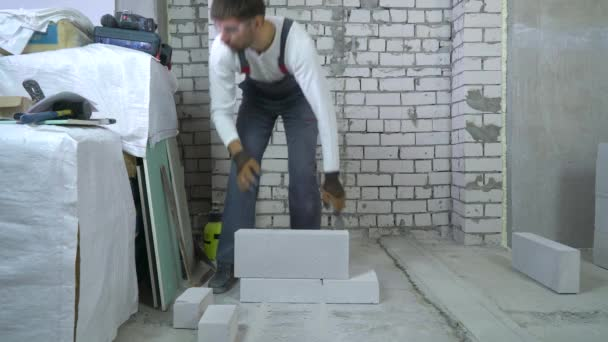 construction worker grinding aerated concrete block at construction site