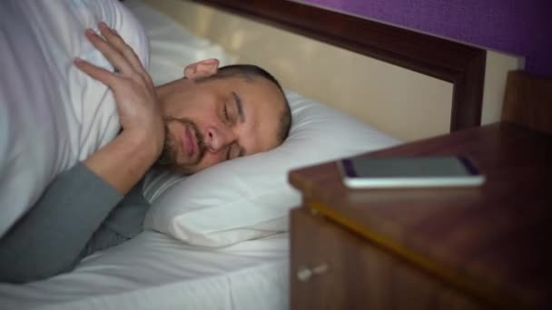 adult man sleeping in bed with phone on bedside table
