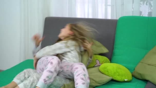 two little girls fighting for fun on sofa