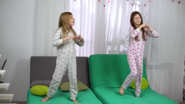 two cute girls in pajamas dancing on sofa. children having fun together at home. friendship, childhood and entertainment