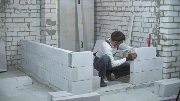 építőmunkás egyenletességét, a szénsav hozzáadásával készült beton fal vízmérték ellenőrzi. egységes és kesztyű Austin belső fal. ház felújítása, építése és kézi munka