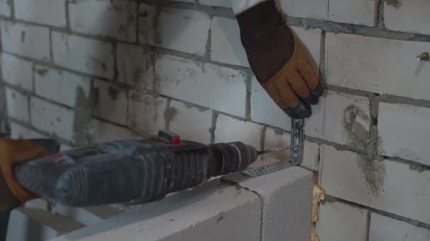 Baumeister, die Löcher in der Mauer mit Bohrmaschine für den Beitritt Klammer Schrauben