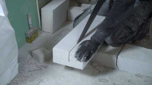 construction worker sawing aerated concrete block according to marking