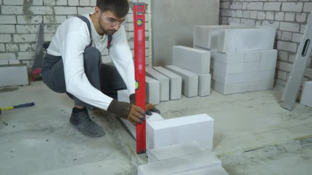 construction worker checking block laying with bubble level