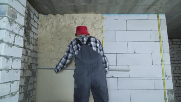 builder spreading plaster on aerated concrete block wall with construction ruler