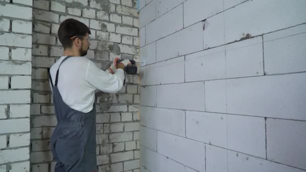 Baumeister, Bohren von Löchern in belüfteten Betonblock Wand mit Bohrmaschine