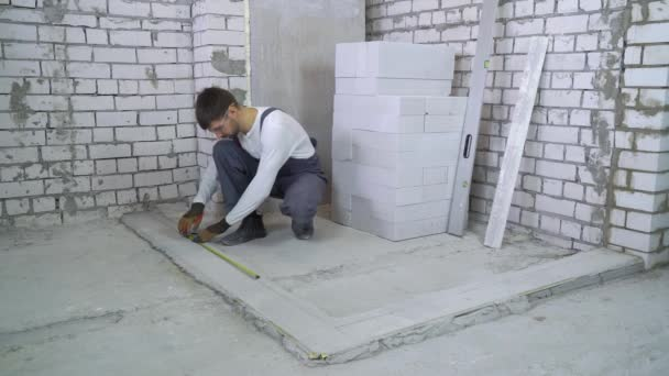 builder measures distances with measuring tape and pencil at construction site