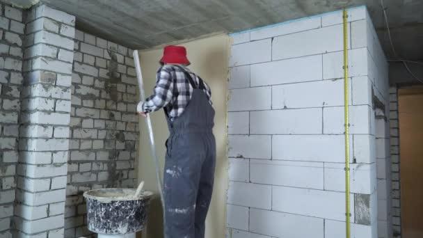 Baumeister Putz auf Nivellierung belüftet Betonblock Wand mit Bau-Lineal