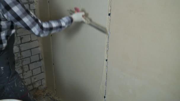 Štukatér vyhladí tlumením sádra na vnitřní stěnu stěrkou volného místa