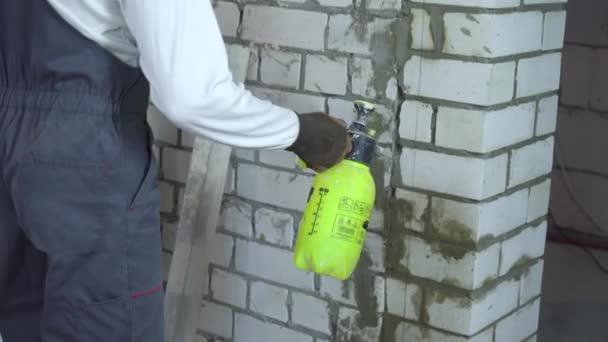 stavební dělník moisturing cihlová zeď s vodou rozprašovačem