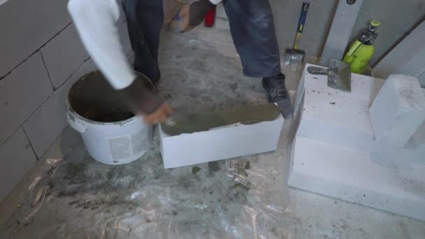 Bauarbeiter legt Klebstofflösung mit Spachtel auf Porenbetonblock