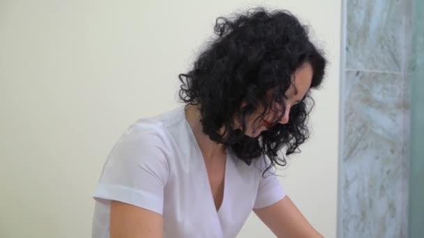 inclinare verso il basso colpo del massaggiatore femminile facendo massaggio anticellulite sulladdome della donna