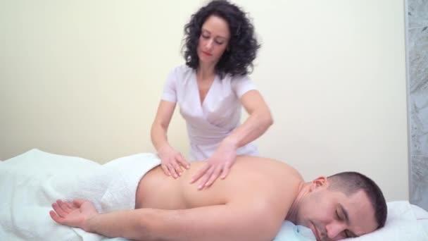 mladá atraktivní žena v jednotné masírovat zadní mužských zákazníků ve spa salonu
