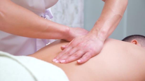 žena ruce dělá, uvolňující masáž zad pro mužského zákazníka ve spa salonu