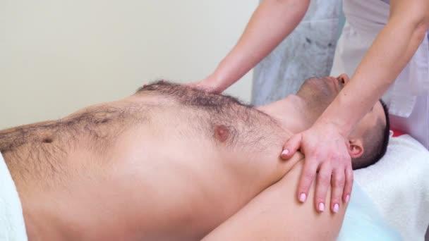 weibliche Hände bei einer entspannenden Massage auf Schultern und Brust des männlichen Patienten