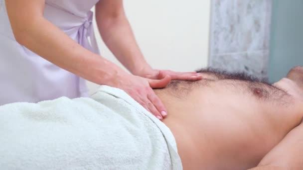 weibliche Hände bei einer entspannenden Massage auf dem Bauch männlicher Kunden im Wellness-Salon