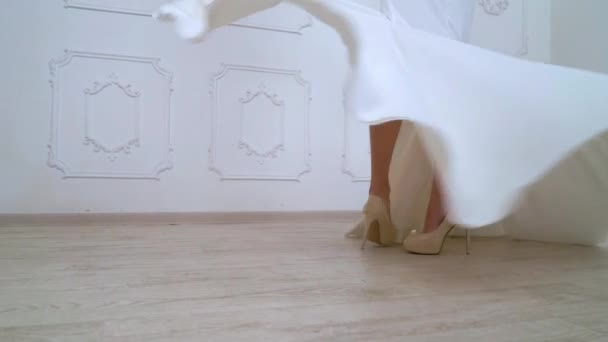 low shot of female legs in high heels and long dress turn around in slow motion