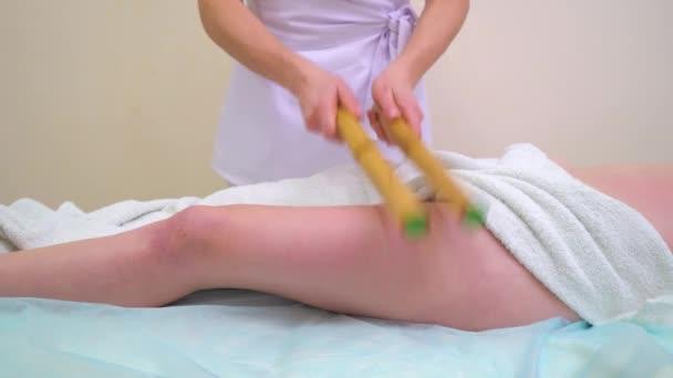 weibliche Masseur anti-Cellulite-Massage auf Frau Oberschenkel mit Bambusstöcken zu tun