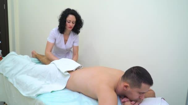 fiatal nő egységes ennek relaxáló masszázs az ember lábát a spa szalon
