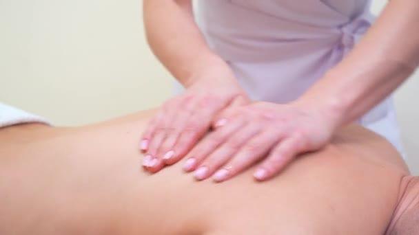 weibliche Hände tun Rückenmassage für männliche Kunden im Wellness-salon