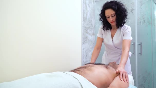 beautiful female therapist massaging shoulders and chest of male customer in spa